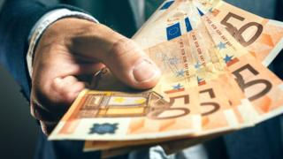 A stock image shows a man holding a handful of €50 notes out in offering