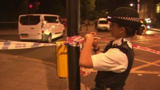 立ち入り禁止のテープを張る警官