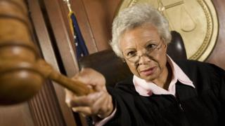 A judge pointing her gavel