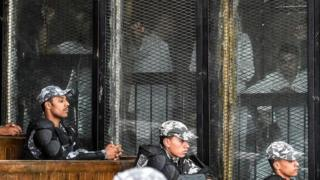 "Members of Egypt""s banned Muslim Brotherhood are seen inside a glass dock during their trial in the capital Cairo on July 28, 2018."