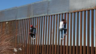 Boys climb border fence at Ciudad Juarez