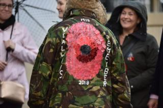 A member of the public wears a jacket with a large poppy on the back