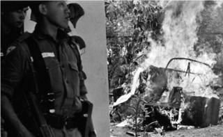 Sejumlah serdadu, tak jauh dari rongsokan sebuah mobil yang terbakar di hari-hari awal oktober 1965, menyusul gagalnya G30S.