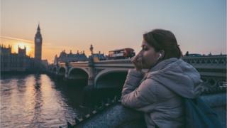 امرأة تضع سماعات التلفون في لندن - نهر التيمز