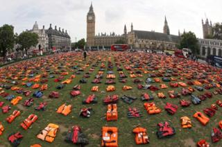 A display of lifejackets worn by refugees during their crossing from Turkey to the Greek island of Chois, are seen Parliament Square in central London