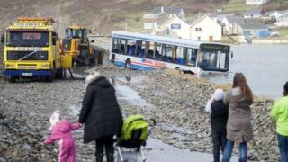 Onlookers watched as the stranded bus was moved on Sunday
