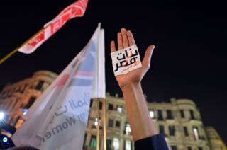 """يد ولافتة مكتوب عليها """"النساء خط أحمر"""""""