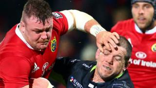 Munster's Dave Kilcoyne is tackled by Paul James of Ospreys