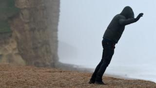 A person leans into the wind in West Bay, Dorset