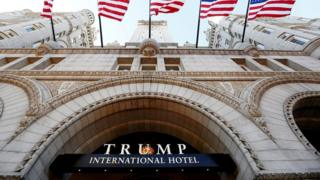 Flags fly above the entrance to the new Trump International Hotel on its opening day in Washington, DC