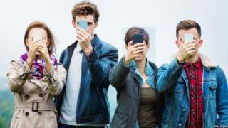 Четыре человека со смартфонами