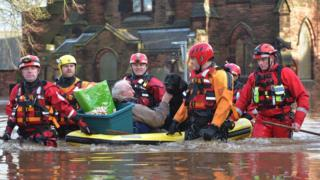 A man and his dog are carried to safety in Carlisle on board a small vessel