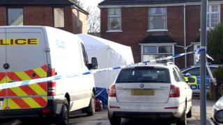 Road cordoned-off and a crime scene tent