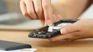 Mujer colocando una tarjeta SIM en un celular