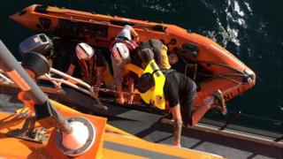 Fishermen being transferred to Alderney's relief RNLI lifeboat
