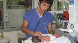 Gonzalo Leiva Rojas cuidando de un bebé cuando hacía prácticas en la universidad. Foto cortesía de Gonzalo Leiva Rojas.
