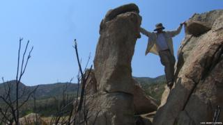one of the researchers straddles a balancing rock in California