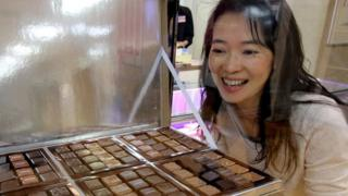 A woman looks at a tray of chocolates