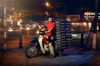 A man posed on a motorcycle with a huge pile of eggs on the back