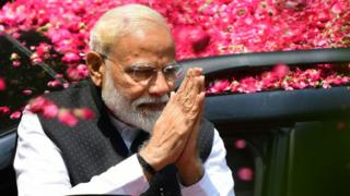 Indian Prime Minister Narendra Modi greets supporters as he arrives to file his election nomination papers in Varanasi.