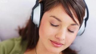 ઇયરફોન પર ગીત સાંભળતી છોકરી