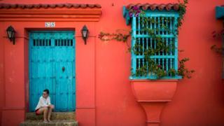 Una mujer está sentada en una escalera en la fachada de una casa del casco colonial de Cartagena de Indias, en Colombia.
