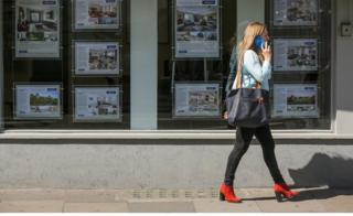 woman walks past estate agent