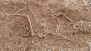 Skeleton of a woman buried in the ground with jewellery