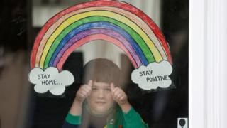 A rainbow drawing is seen as Jake Weller looks through the window of his house as the spread of the coronavirus disease (COVID-19) continues, Aylesbury, Britain