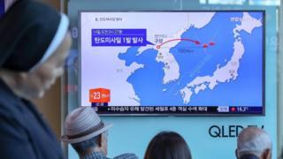 首尔火车站群众收看电视上有关朝鲜发射导弹报道的乘客与路人(14/5/2017)