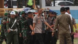 Indonesian police and military carry Wiranto on a stretcher to a helicopter