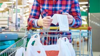 Shopper scrutinising receipt