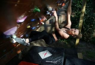 A climber hangs from an outdoor climbing wall