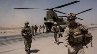 .S. service members walk off a helicopter on the runway at Camp Bost on September 11, 2017 in Helmand Province, Afghanistan.
