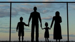 Силуэты семьи на фоне забора из проволоки