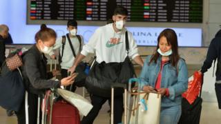 Travellers wearing surgical masks at an airport