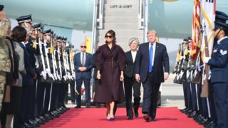 한국을 첫 방문한 트럼트 대통령과 부인 멜라니아 여사와 뒤로 영접을 나온 한국의 강경화 외교부 장관이 함께 활주로를 걷고 있다.