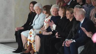 女王破天荒來看秀,在英國新人設計師理查德·昆尼(Richard Quinn)的秀場前排就座,陪同女王左右的分別為英國時裝協會負責人卡羅琳·拉什(Caroline Rush)和時尚魔頭、《Vogue》美國版主編、電影《穿PRADA的惡魔》的原型安娜·溫圖爾。
