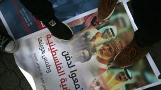 جانب من مظاهرة يدوس فيها المتظاهرون صورة لحكام عرب وكوشنر