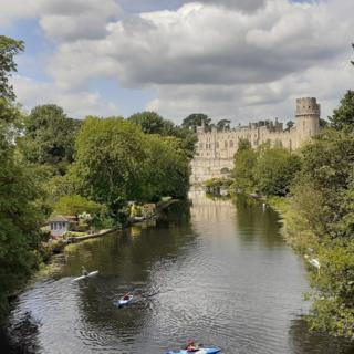 People kayaking on the River Avon, with Warwick Castle in the background