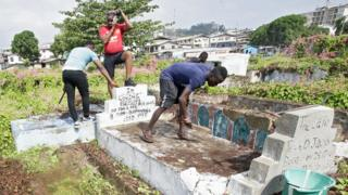 in_pictures Men cleaning graves at Palm Groove Cemetery in Monrovia, Liberia - Wednesday 11 March 2020
