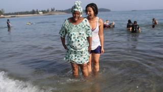 A Congolese woman stands in the ocean for the first time guided by an American woman during during a programme to help integrate new refugees in Maine, the US - Tuesday 28 August 2018