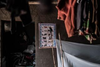 An educational poster hangs on the wall of Lona Kiji's home in Bidi Bidi refugee camp