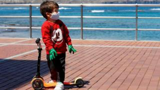 A child plays with a scooter at promenade of Las Canteras beach after restrictions were partially lifted for children for the first time in six weeks