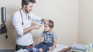 семейный доктор замеряет мальчику температуру