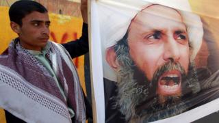 متظاهر يرفع صورة الشيخ نمر النمر
