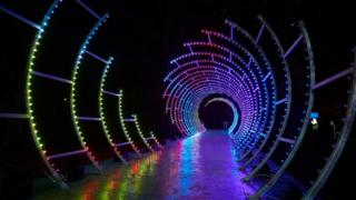 A-spiral-of-multicoloured-light-with-a-walkway-running-through-it.