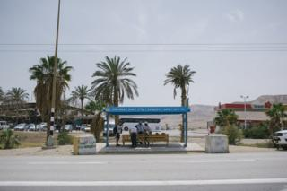 Orthodox Jewish boys sit in the shade at a bus stop near the Palestinian town of Jericho in West Bank