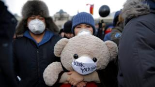Mongolian protesters carry a stuffed toy teddy bear wearing a face mask, as the protest against air pollution in Ulaanbaatar