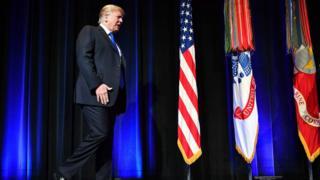 Donald Trump caminha em palco em direção ao púlpito, com bandeiras ao fundo
